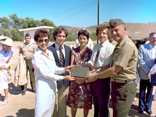 MGEN Stephen G. Olmstead, commanding general, Marine Corps Base, Camp Pendleton, and the family of the late MGEN Edward A. Wilcox, including his wife, Mrs. Edward A. Wilcox, their daughter and two sons hold a plaque in honor of general. Rifle Range 103 was renamed Wilcox Range in honor of the general who died in early 1980. Standing to the right of GEN Olmstead and behind one of the sons is GEN Kenneth McLennan, assistant commandant of the Marine Corps