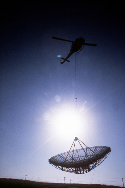 A helicopter airlifts a radar antenna disc from one tracking station to another on the base. AAVS PHOTO Contest Entry, color, Sept. 1980