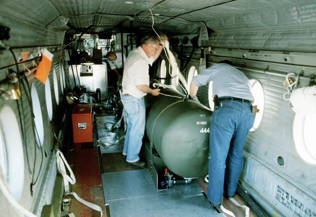 A civilian crew from the Environmental Research Institute of Michigan prepare an auxiliary fuel tank for removal from inside a C-7 Caribou aircraft