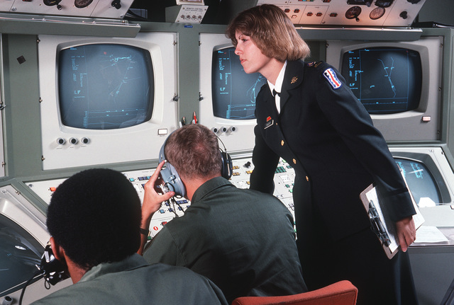 A female US Army officer observes students working at a missile radar training console
