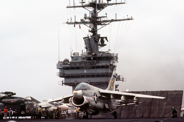 A left front view of an A-7 Corsair II aircraft preparing to launch from the flight deck of the nuclear-powered aircraft carrier USS DWIGHT D. EISENHOWER (CVN-69). A CH-53 Sea Stallion helicopter is parked to the left