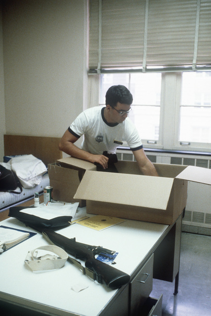 A plebe unpacks as he moves into his quarters at the US Naval Academy. An M1 rifle is on the table