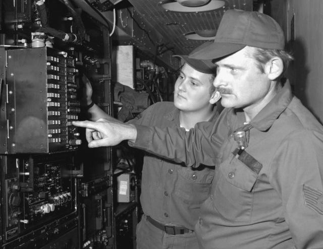 A radar maintenance technician explains functions of radar equipment to an airman in an air traffic control section
