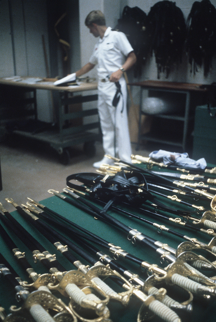 A senior midshipman checks the ceremonial swords to be issued to plebes when they check in at the US Naval Academy