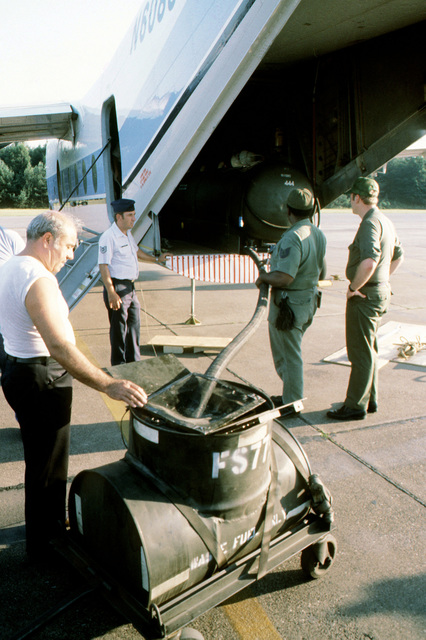 A technical sergeant, hand on plane, watches as an auxiliary fuel tank is defueled before removal from a C-7 Caribou aircraft for storage