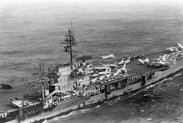 An aerial starboard view of the amidships section of the Kitty Hawk class aircraft carrier USS CONSTELLATION (CV 64), as an A-6E Intruder aircraft makes a catapult assisted takeoff from the flight deck