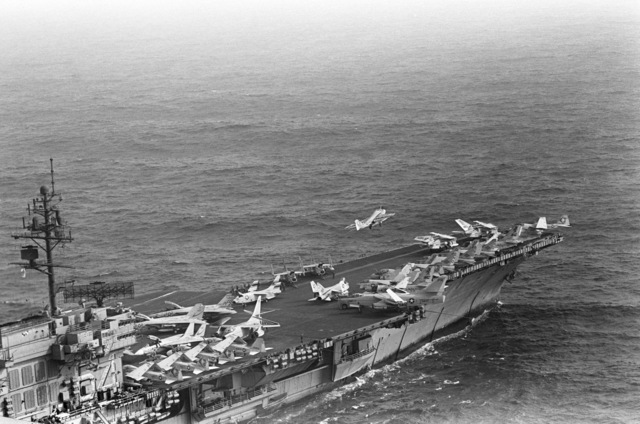 An aerial starboard view of the forward section of the Kitty Hawk class aircraft carrier USS CONSTELLATION (CV 64), as an A-6E Intruder aircraft begins to bank to the left after a catapult assisted takeoff from the flight deck