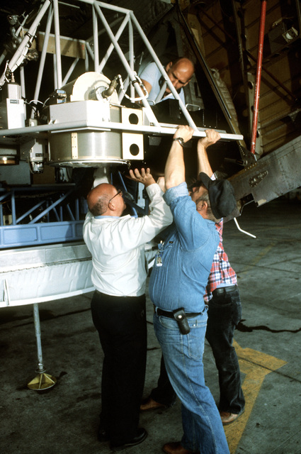 Civilian members of the Environmental Research Institute of Michigan install equipment onto a pallet