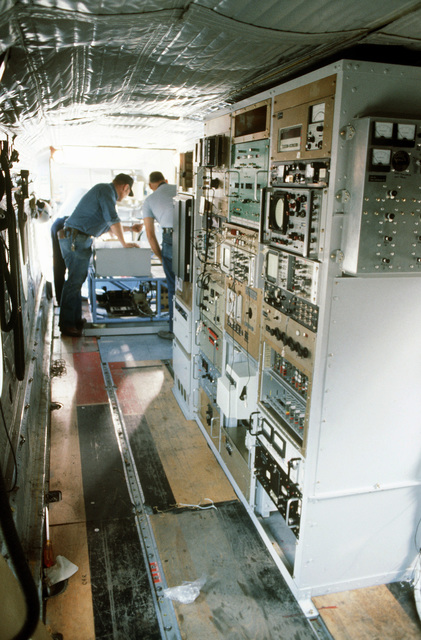 Interior view of a C-7 Caribou aircraft with civilian personnel from the Environmental Research Institute of Michigan loading pallets aboard