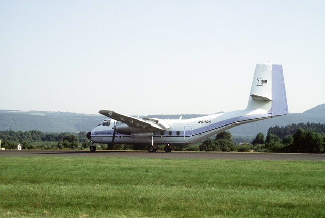 Left side view of a C-7 Caribou aircraft landing. Aboard are members of the Environmental Research Institute of Michigan