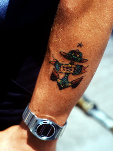 The tattooed forearm of a sailor assigned to the Naval Training Center, Recruit Training Command