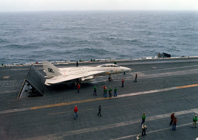 A left front view of a Fighter Squadron 142 (VF-142) F-14 Tomcat aircraft being prepared for a catapult-assisted takeoff from the flight deck of the nuclear-powered aircraft carrier USS DWIGHT D. EISENHOWER (CVN-69). Three blast deflector panels are raised at the rear of the aircraft