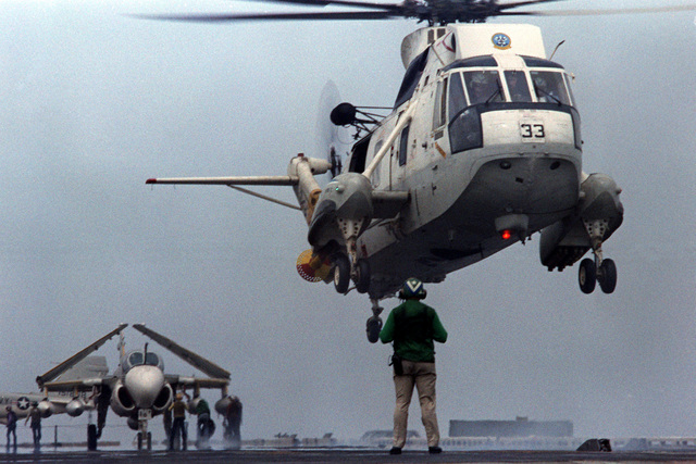 A plane director guides an SH-3 Sea King helicopter to a landing on the flight deck of the nuclear-powered aircraft carrier USS DWIGHT D. EISENHOWER (CVN-69). The SH-3 is assigned to Helicopter Squadron 5 (HS-3). Third view in a series of five