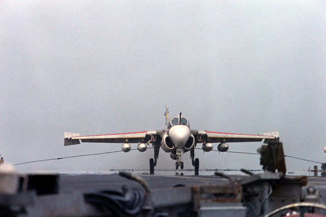 An A-6E Intruder aircraft engages the arresting cable during a landing on the flight deck of the nuclear-powered aircraft carrier USS DWIGHT D. EISENHOWER (CVN-69). The A-6E is assigned to Medium Attack Squadron 65 (VA-65)