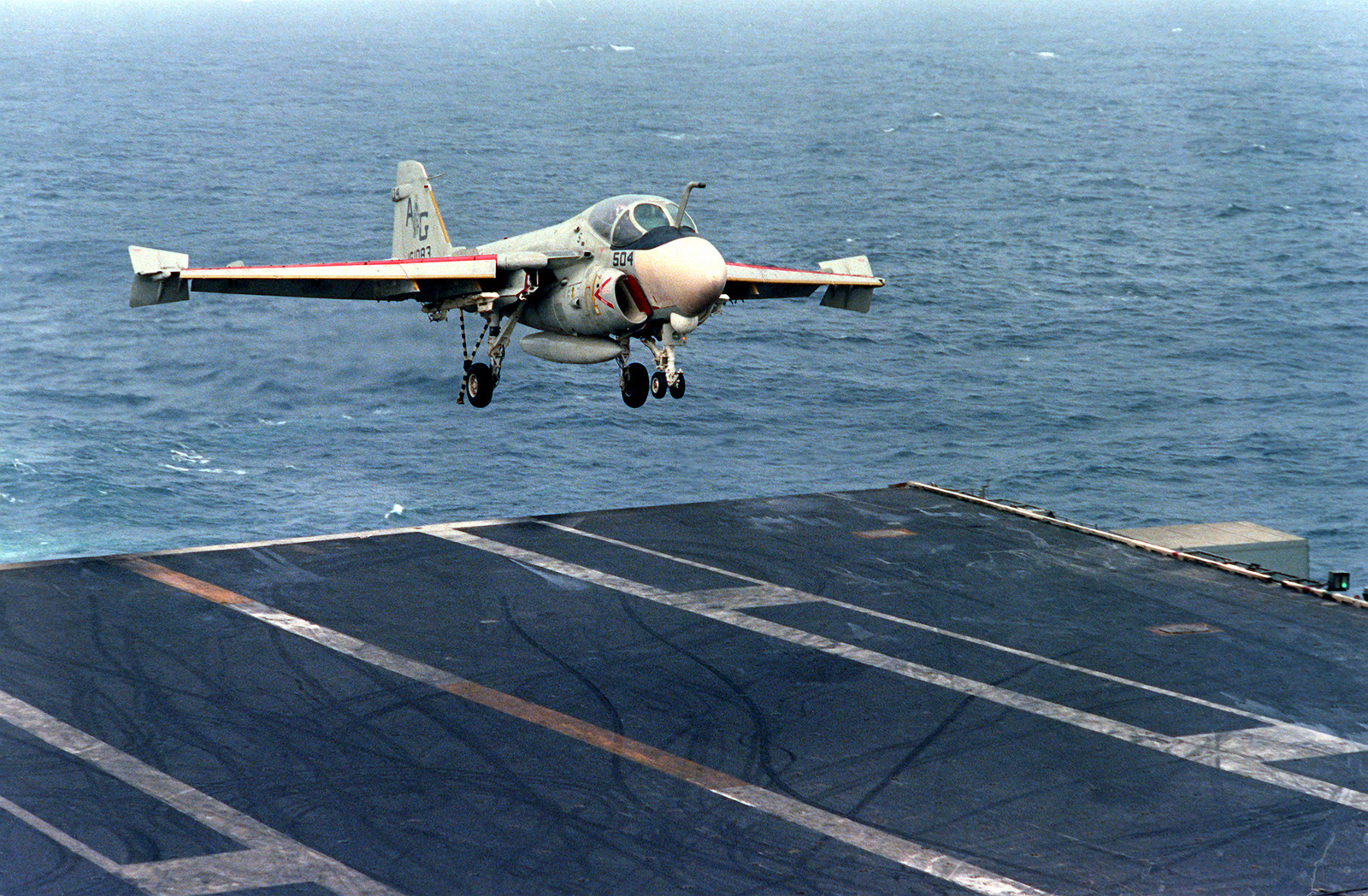 An A-6E Intruder aircraft prepares to touch down on the flight deck during an arrested landing aboard the nuclear-powered aircraft carrier USS DWIGHT D. EISENHOWER (CVN-69). The A-6E is assigned to Medium Attack Squadron 65 (VA-65)