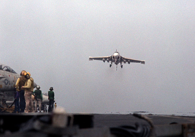 An A-6E Intruder aircraft, with its arresting hook down, approaches for a landing on the flight deck of the nuclear-powered aircraft carrier USS DWIGHT D. EISENHOWER (CVN-69). The A-6E is assigned to Medium Attack Squadron 65 (VA-65). Second view in a series of eight