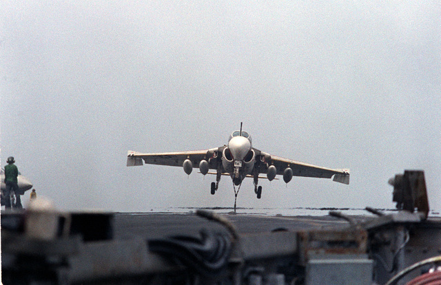 An A-6E Intruder aircraft, with its arresting hook down, approaches for a landing on the flight deck of the nuclear-powered aircraft carrier USS DWIGHT D. EISENHOWER (CVN-69). The A-6E is assigned to Medium Attack Squadron 65 (VA-65). Fourth view in a series of eight