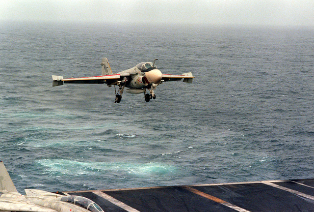 An A-6E Intruder aircraft, with its arresting hook down, approaches for a landing on the flight deck of the nuclear-powered aircraft carrier USS DWIGHT D. EISENHOWER (CVN-69). The A-6E is assigned to Medium Attack Squadron 65 (VA-65)