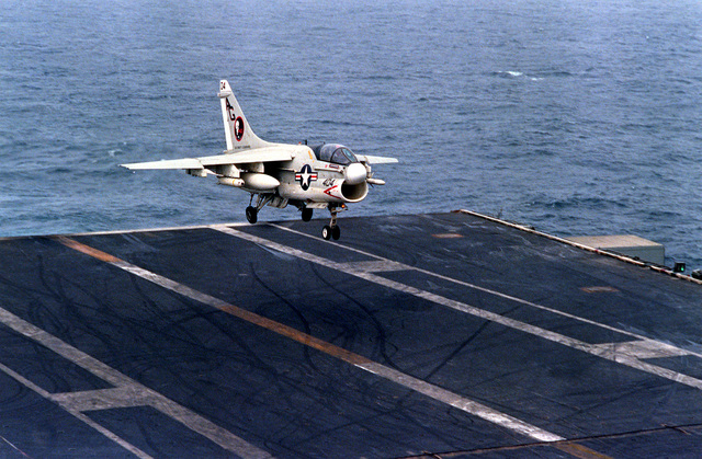 An A-7E Corsair II aircraft prepares to touch down on the flight deck during an arrested landing aboard the nuclear-powered aircraft carrier USS DWIGHT D. EISENHOWER (CVN-69). The A-7E is assigned to Light Attack Squadron 12 (VA-12)