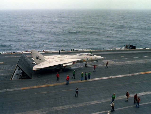 An elevated left side view of an F-14 Tomcat aircraft being prepared for a catapult-assisted takeoff from the flight deck of the nuclear-powered aircraft carrier USS DWIGHT D. EISENHOWER (CVN-69). The F-14 is assigned to Fighter Squadron 142 (VF-142). Three blast deflector panels are raised at the rear of the aircraft