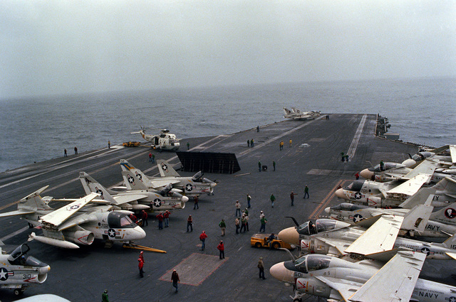 An elevated view of the forward section of the flight deck of the nuclear-powered aircraft carrier USS DWIGHT D. EISENHOWER (CVN-69) during aircraft launch and recovery operations. Parked behind the raised blast deflector panels are three A-7E Corsair II aircraft and an S-3 Viking aircraft. On the starboard side of the flight deck are four A-6E Intruder aircraft, an S-3 and an A-7E