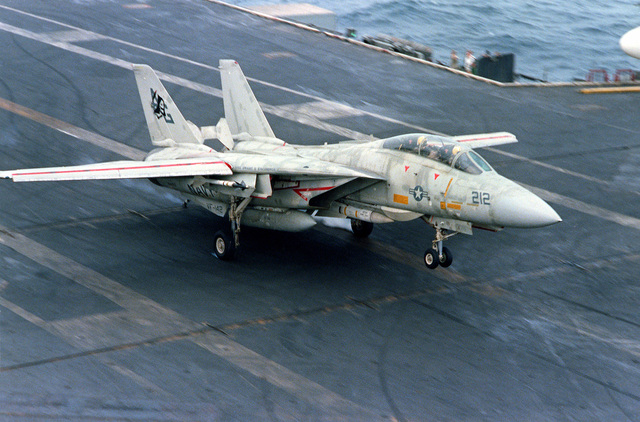 An F-14 Tomcat aircraft makes an arrested landing on the flight deck of the nuclear-powered aircraft carrier USS DWIGHT D. EISENHOWER (CVN-69). The F-14 is assigned to Fighter Squadron 142 (VF-142)