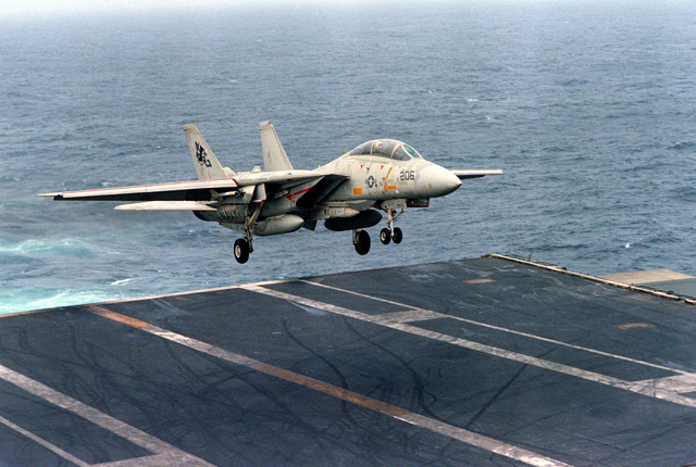 An F-14 Tomcat aircraft prepares to touch down on the flight deck during an arrested landing aboard the nuclear-powered aircraft carrier USS DWIGHT D. EISENHOWER (CVN-69). The F-14 is assigned to Fighter Squadron 142 (VF-142)