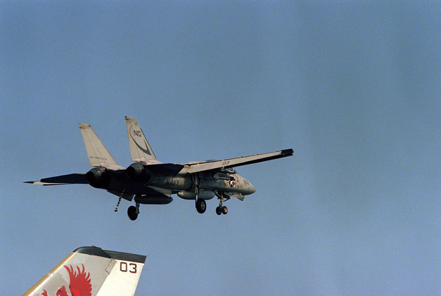 An F-14 Tomcat aircraft, with arresting hook down, makes a pass over the flight deck during launch and recovery operations aboard the nuclear-powered aircraft carrier USS DWIGHT D. EISENHOWER (CVN-69)