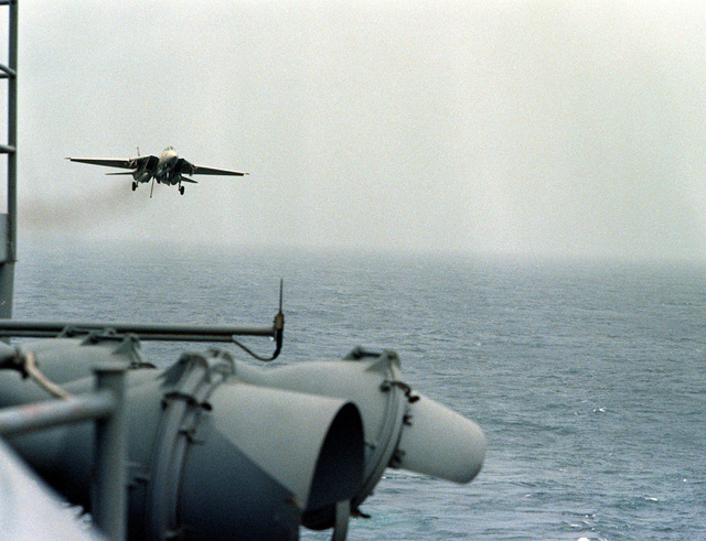 An F-14 Tomcat aircraft, with arresting hook lowered, approaches for a landing on the flight deck of the nuclear-powered aircraft carrier USS DWIGHT D. EISENHOWER (CVN-69)