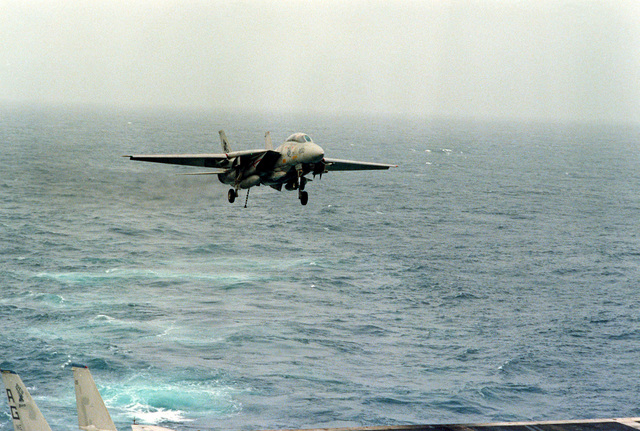 An F-14 Tomcat aircraft, with its arresting hook down, approaches for a landing on the flight deck of the nuclear-powered aircraft carrier USS DWIGHT D. EISENHOWER (CVN-69). The F-14 is assigned to Fighter Squadron 142 (VF-142)