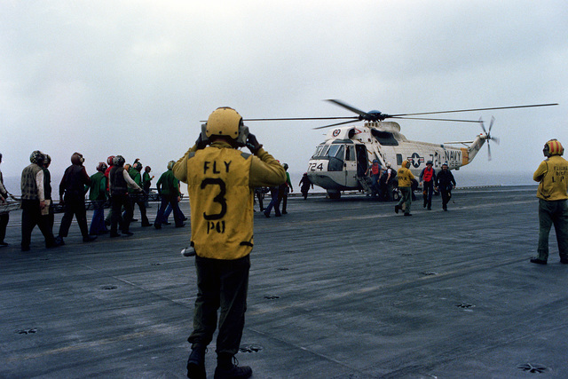 Flight deck personnel carry stretchers to a waiting SH-3 Sea King helicopter during flight operations aboard the nuclear-powered aircraft carrier USS DWIGHT D. EISENHOWER (CVN-69). The SH-3 is assigned to Helicopter Squadron 6 (HS-6)