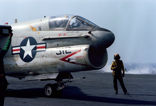 Plane directors signal instructions to the pilot of an A-7E Corsair II aircraft during launch and recovery operations aboard the nuclear-powered aircraft carrier USS DWIGHT D. EISENHOWER (CVN-69)