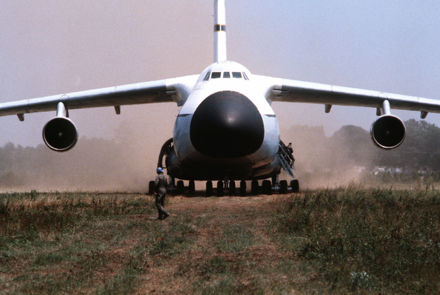 A front view of a C-5A Galaxy aircraft taxiing in the dirt during an operational utility evaluation test