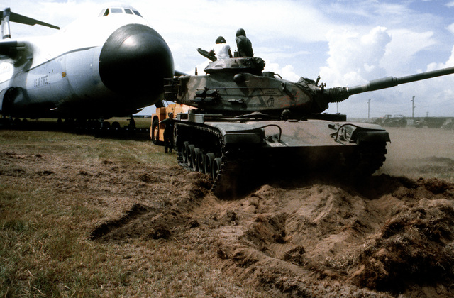 A right front view of an M-60A1 main battle tank helping tow a C-5A Galaxy aircraft across sandy terrain during an operational utility evaluation test for aircraft