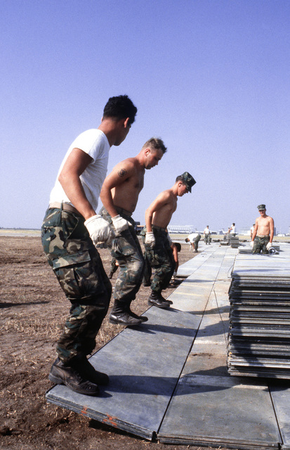 Marines install matting for a portable runway during a C-5A Galaxy aircraft operational utility evaluation test