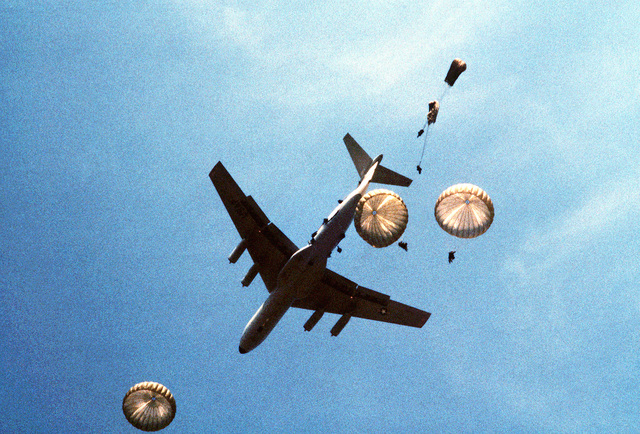A C-141 Starlifter aircraft drops members of the 82nd Airborne Division over the drop zone during exercise Dragon Team