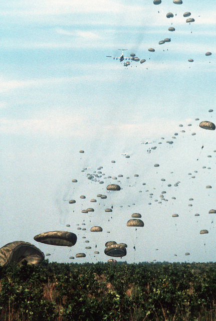 C-141 Starlifter aircraft drop members of the 82nd Airborne Division over the drop zone during exercise Dragon Team