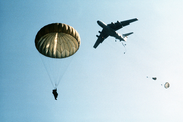 Members of the 82nd Airborne Division jump from a C-141 Starlifter aircraft during exercise Dragon Team