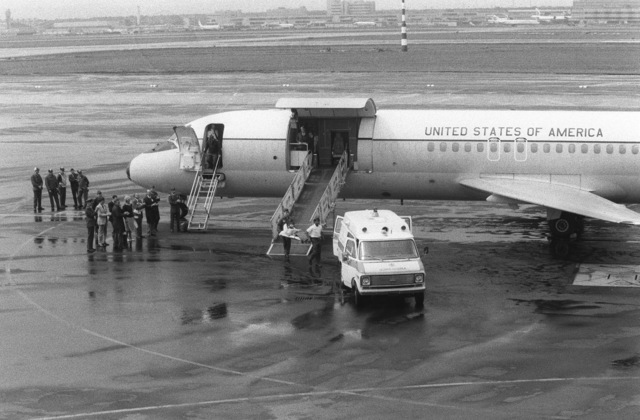 Ex-Iranian hostage Richard Queen is carried from a C-9 Nightingale aircraft of the 55th Aeromedical Airlift Squadron to a waiting ambulance. Queen, an American diplomat who was held hostage for 250 days, was transferred here from Zurich, Switzerland, for treatment at the US Air Force Regional Medical Center Weisbaden. Base and state department officials and his parents look on
