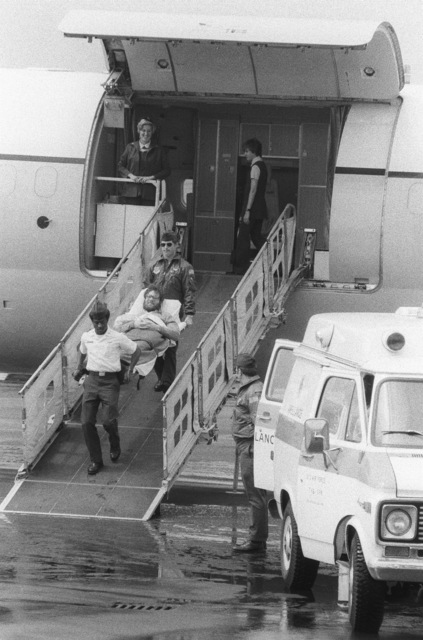 STAFF Sergeants (SSGT) Dennis Puffer, rear, and SSGT Philip Earley carry ex-Iranian hostage Richard Queen from a C-9 Nightingale aircraft of the 55th Aeromedical Airlift Squadron to a waiting ambulance. Queen, an American diplomat who was held hostage for 250 days, was transferred here from Zurich, Switzerland, for treatment at the US Air Force Regional Medical Center Weisbaden