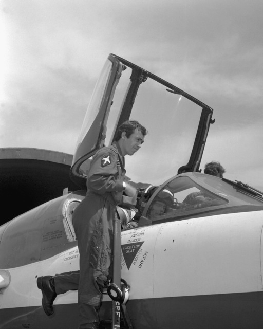 A Royal Air Force pilot assists a U.S. Air Force pilot aboard an aircraft during an RAF visit to the base