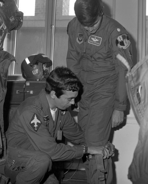 A Royal Air Force pilot helps a U.S. Air Force pilot don his flight suit during an RAF visit to the base