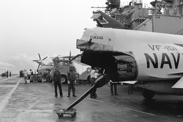 A view of the damaged tail section of an F-4J Phantom II aircraft on the flight deck of the aircraft carrier USS MIDWAY (CV 41). The damage resulted from a collision between the MIDWAY and the Panamanian freighter CACTUS