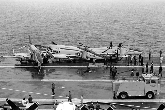 A view of the flight deck of the aircraft carrier USS MIDWAY (CV 41) as crewmen work to recover a damaged F-4J Phantom II aircraft hanging off the side of the ship. The damage resulted from a collision between the MIDWAY and the Panamanian freighter CACTUS