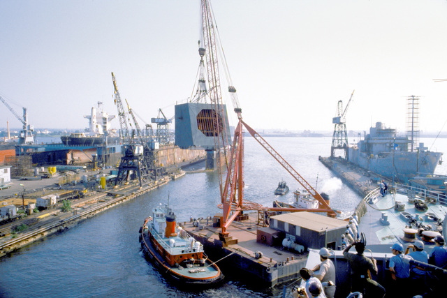 A lift barge/crane, being propelled by a tugboat on each side, carries the radar turret aboard the USNS OBSERVATION ISLAND (T-AGM-23) which is being converted to a missile and satellite tracking station. The conversion operation is called Project Cobra Judy