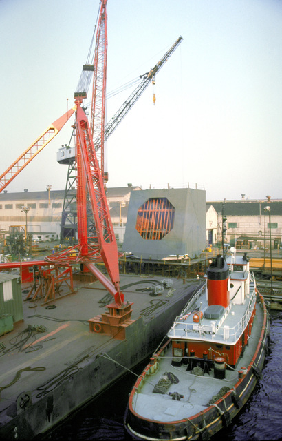 A lift barge/crane, being propelled by a tugboat on each side, moves into position to lift the radar turret aboard the USNS OBSERVATION ISLAND (T-AGM-23) which is being converted to a missile and satellite tracking station. The conversion operation is called Project Cobra Judy