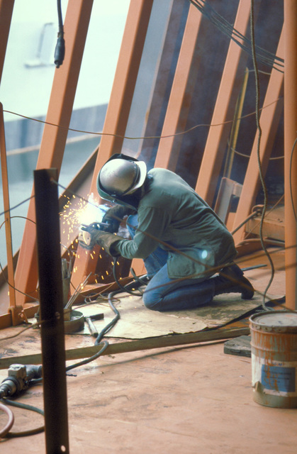 A welder of the puts finishing touches on a radar turret aboard the USNS OBSERVATION ISLAND (T-AGM-23) which is being converted to a missile and satellite tracking station. The ship conversion operation is called Project Cobra Judy