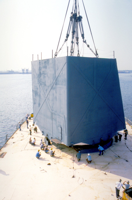 The radar turret is being lifted o onto the stern of the USNS OBSERVATION ISLAND (T-AGM-23) which is being converted to a missile and satellite tracking station. The conversion operation is called Project Cobra Judy