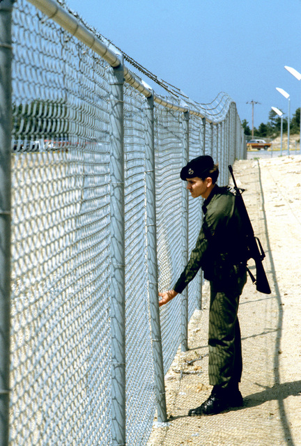 A Strategic Air Command security policeman checks the chain link fence enclosing the Pave Paws Radar Site, at the Cape Cod Missile Early Warning Station, during a perimeter patrol