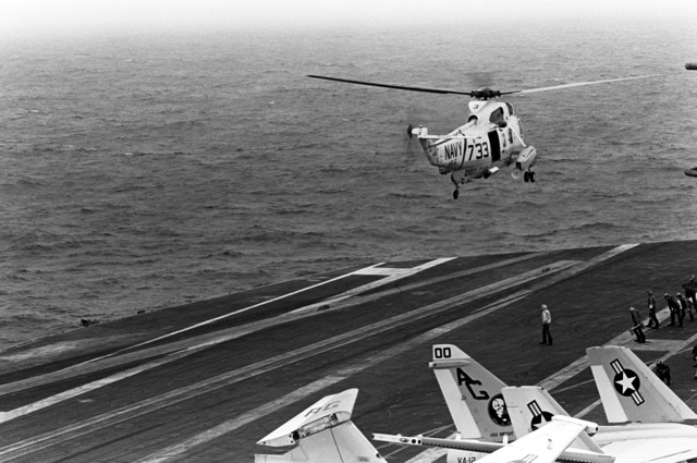 An SH-3 Sea King helicopter takes off from the flight deck during flight operations aboard the nuclear-powered aircraft carrier USS DWIGHT D. EISENHOWER (CVN-69). The SH-3 is assigned to Helicopter Squadron 5 (HS-5). Note: Third view in a series of five
